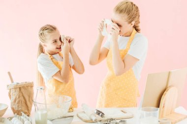Happy mother and daughter looking at each other with dough pieces while preparing cookies isolated on pink stock vector
