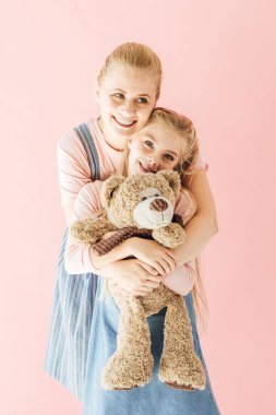 Smiling mother and daughter with teddy bear embracing isolated on pink stock vector