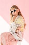 roztomilá módní mladík v trendy brýle pózuje na růžové