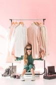 Photo fashionable preteen child sitting near clothes and footwear in boutique