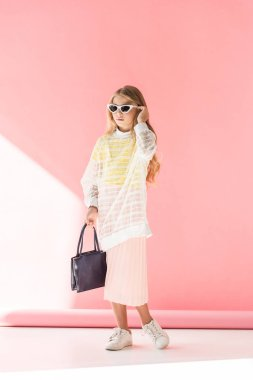 blonde fashionable youngster in sunglasses posing with bag on pink