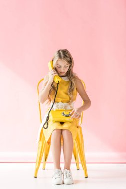 adorable youngster making call with rotary telephone while sitting on yellow chair on pink