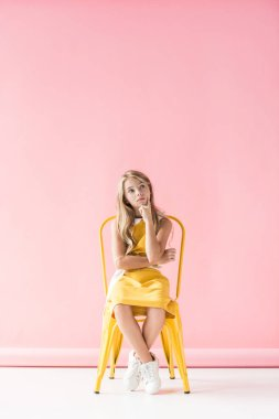 thoughtful preteen kid in fashionable clothing sitting on yellow chair on pink