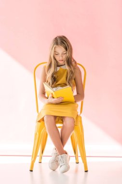 charming female youngster reading book while sitting on yellow chair on pink