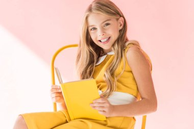happy stylish child reading book while sitting on yellow chair on pink