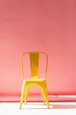 Studio shot of trendy yellow chair and on pink stock vector