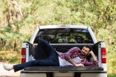 Happy vousatý muž relaxační na pick-up v lese