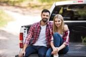 Fotografie usmívající se pár objímat a seděli na pick-up