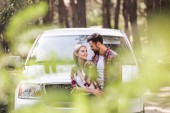 selective focus of happy couple hugging at pickup truck in forest
