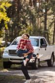 Fotografia coppie emozionanti divertendosi insieme nella foresta con camioncino dietro
