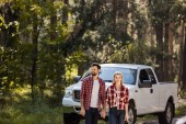 beautiful couple holding hands and standing near pickup truck in forest