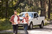 Fotografie excited couple holding hands and running from pickup truck, woman showing something in forest