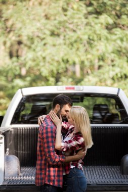 beautiful young couple hugging and going to kiss near car in forest