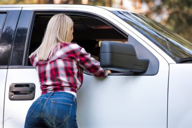 back view of blonde girl standing near white pickup truck