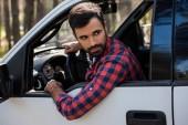 Fotografia barbuto autista che regge al volante in camioncino nella foresta