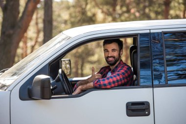 Bearded driver showing thumb up while sitting in pickup truck in forest stock vector