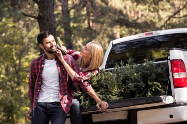Girlfriend trying to shaving boyfriend with axe while sitting on pickup truck with fir tree for christmas in forest