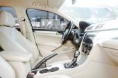 Fotografia immagine potata di auto nuova in pelle e volante posti sulla strada