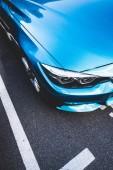 oříznutý obraz modré lesklé nové auto na ulici