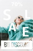 Fotografie beautiful stylish child in turquoise fur coat lying with black shopping bag on white, big discount sale banner concept