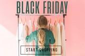 Heckansicht des blonden Kind im trendigen Overall Wahl Kleidung auf Kleiderbügeln, schwarzen Freitag verkaufen Banner Konzept