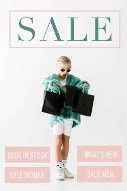 shocked kid in stylish fur coat looking into black shopping bags isolated on white, sale banner concept