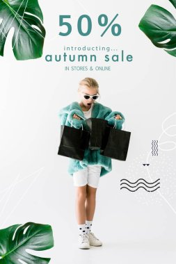 shocked kid in stylish fur coat looking into black shopping bags isolated on white, autumn sale banner concept