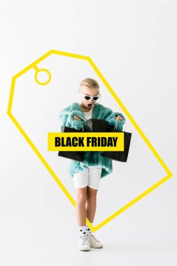 shocked kid in stylish fur coat looking into black shopping bags isolated on white, black friday sale banner concept