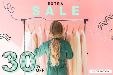 rear view of blonde kid in trendy overalls choosing clothes on hangers, sale banner concept