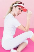 Fotografie stylish female athlete in visor hat posing on pink