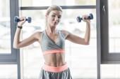Fotografie hübsche junge Frau, die das Training mit Hanteln im Fitnessstudio