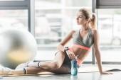 Selektivní fokus sportovní ženy s smartwatch odpočívá s sportovní láhev vody poblíž fitness míč v tělocvičně
