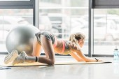 Fotografie rear view of female athlete doing exercise on fitness mat at sports hall