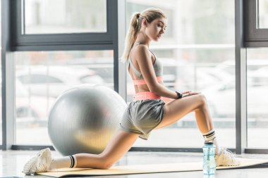 side view of sportswoman doing exercise on fitness mat at sports hall