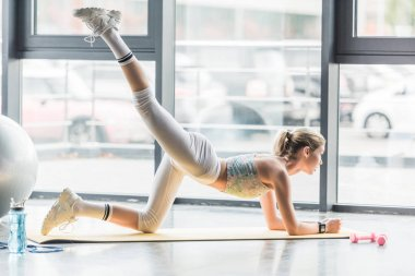 side view of young sportswoman stretching on fitness mat at gym
