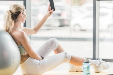 selective focus of sportswoman with earphones taking selfie on smartphone at gym