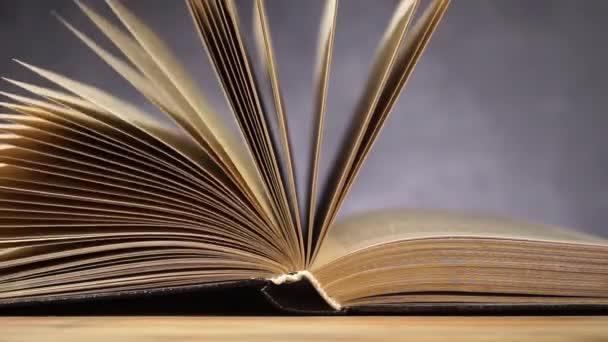 Knihy o starý dřevěný stůl. Krásné tmavé pozadí.
