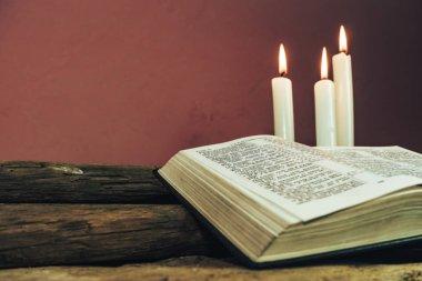 Yakın güzel açık İncil ve eski bir meşe ahşap masa ve kırmızı duvar arka plan üzerinde üç beyaz yanmış mumlar kadar.