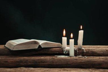 Güzel açık İncil ve eski bir meşe ahşap masada mumlar yandı. Dumanın arka planı.