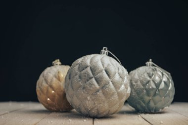 Beautiful Christmas baubles on a new wooden table fell by snow and black  background behind.