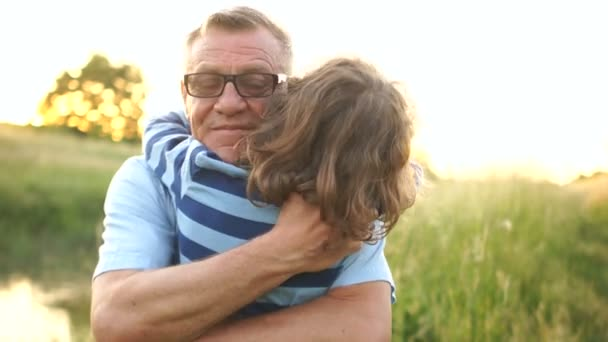 Close-up of a grandfather hugging his grandson. The curly-haired boy resorts to his grandfather. The continuity of generations. Happy family