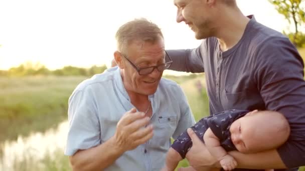 Three generations of men. Grandpa, father and little grandson. Father and son greet each other with a handshake. Sunset, the bank of the river