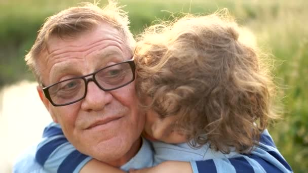 Lovely curly grandson hugs his grandfather. A pensioner in optical glasses with his grandson a schoolboy on the river bank. Happy Family Vacation