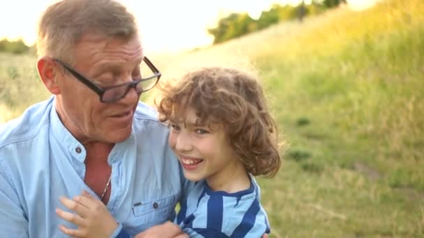 Großvater kitzelt munter seinen Enkel. Sommerferien. Zwei Generationen. lieblicher Lockenkopf. Reifer Mann mit optischer Brille