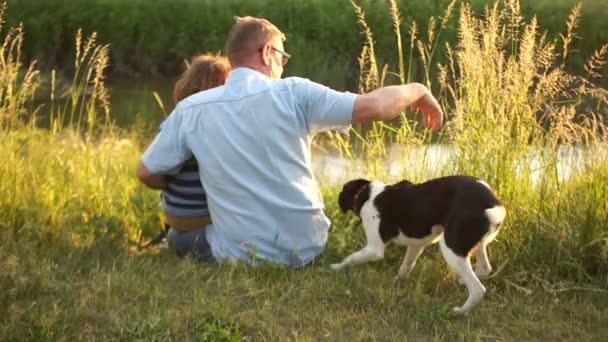Starší muž a chlapec se svým psem sedí na břehu řeky. Přátelskou konverzaci, mužský konverzace, západ slunce, šťastný víkend
