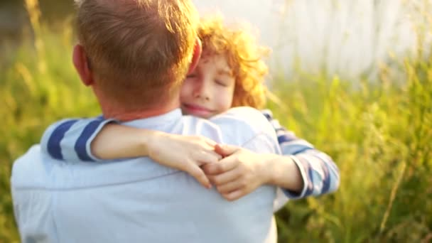 A fiú, és az érett apja ül a folyó partján. Naplemente. A fiú apja vállán szorosan ölelést. Apák napja. Egy boldog család