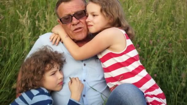 Grandfather and grandchildren. Children hug their beloved grandfather. Family holiday in nature. Carefree pension