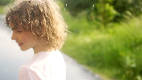 A wonderful child walks in the rain on a wet road. The boy breaks and sings songs. Sunset and summer rain. Childrens Day