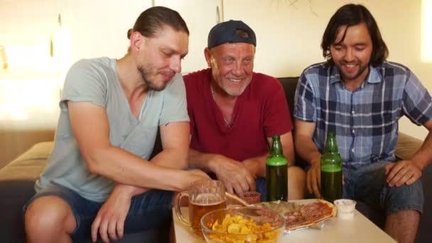 Férfiak felvidítani a kedvenc focicsapat a Tv közelébe. Sört inni, és enni pizzát. Férfi hétvége