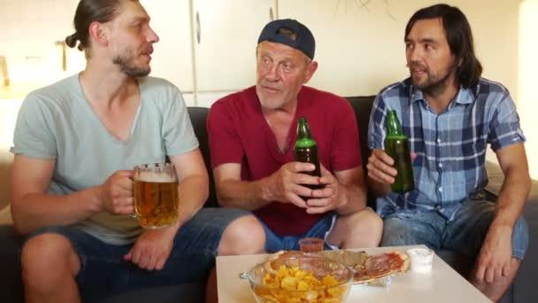 Apa és két fia inni sört. Alkohol egészségügyi kárt. Három férfi inni sört vidáman beszél egymással